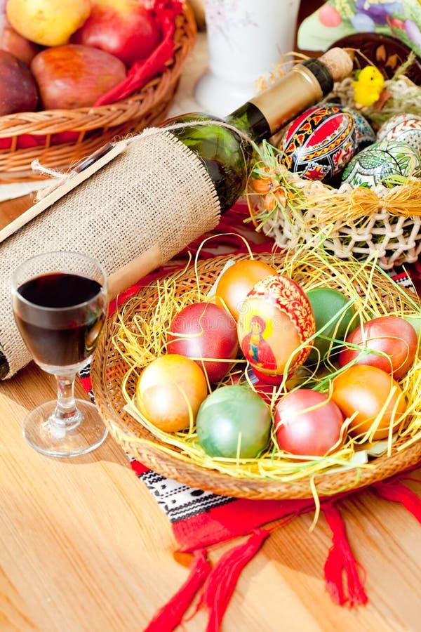 Pasen geschilderde eieren met wijnfles en glas stock foto