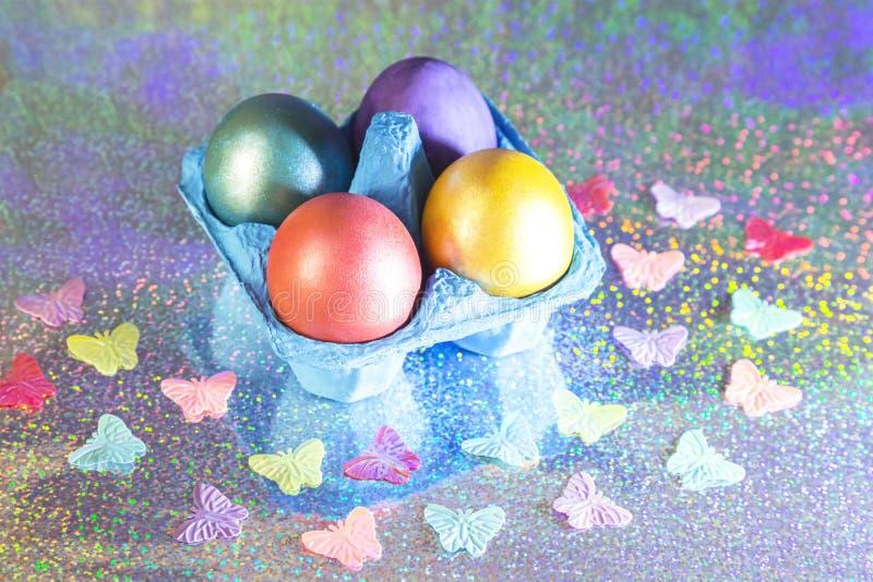 Pasen Geschilderde eieren van gele, roze, purpere, groene, turkooise parelkleur in blauwe verpakking op een holografische regenbo royalty-vrije stock foto