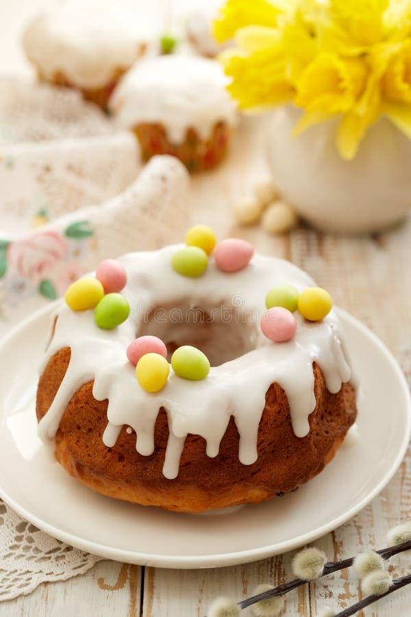 Pasen-gistcake Babka met suikerglazuur wordt en met marsepeineieren wordt verfraaid behandeld die op een witte plaat op een houte royalty-vrije stock foto