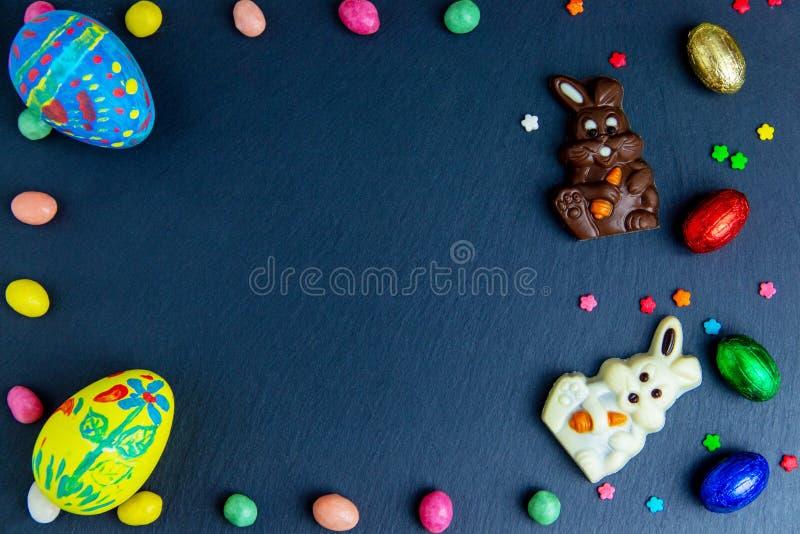 Pasen-groetkaart met kleurrijk suikergoedkader en paasei, chocoladekonijntje en eieren stock fotografie