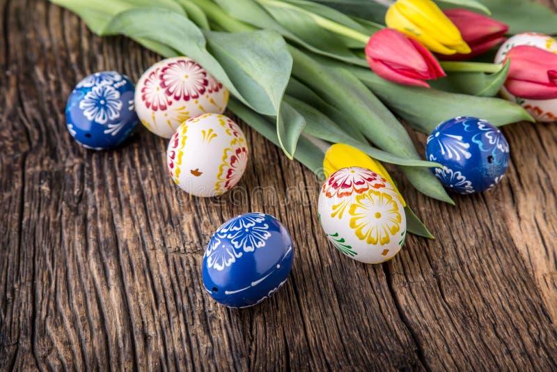 Pasen Hand - gemaakte paaseieren en de lentetulpen op oude houten lijst stock fotografie