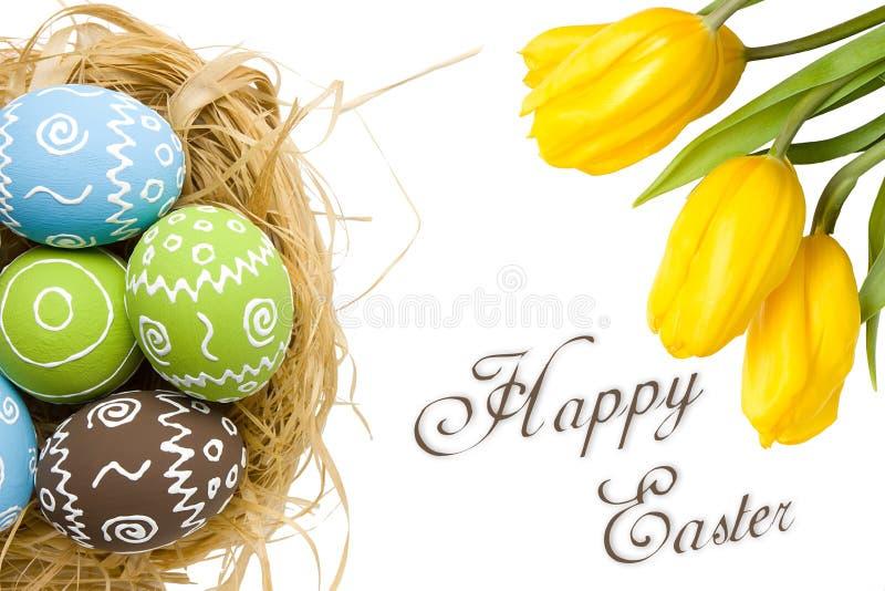 Pasen-kaart met kleurrijke eieren in nest en gele tulpen over witte achtergrond Hoogste mening met exemplaarruimte royalty-vrije stock foto's