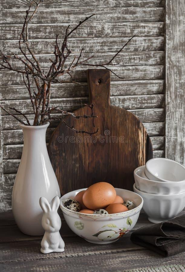 Pasen-keukenstilleven - eieren in een kom, een vaas met droge takjes, ceramisch konijn, uitstekend aardewerk en scherpe raad stock foto