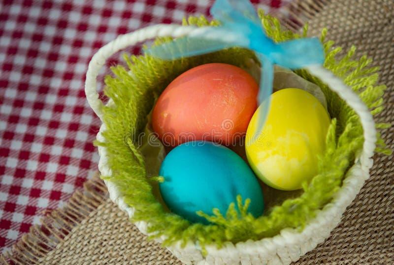 Pasen kleurde eieren in een mand op een canvasservet en een geruit tafelkleed stock afbeeldingen