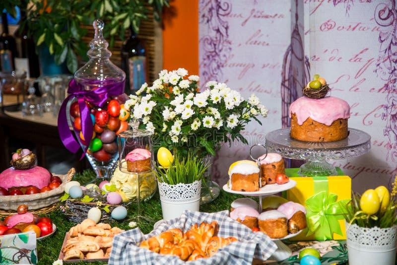 Pasen-lijst: cakes met gekleurde glans op tribunes, gekleurde eieren en boeketten van bloemen stock afbeelding