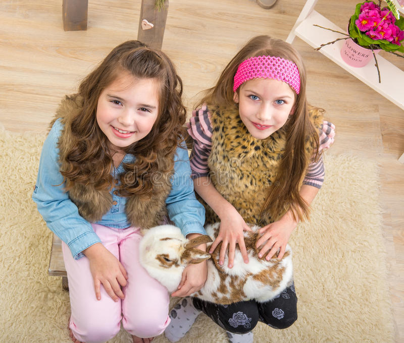 Pasen - Meisjes die het reusachtige, levende konijntje strijken stock fotografie