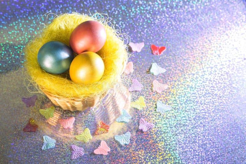 Pasen Multicolored Geschilderde eieren van gele, roze, groene, turkooise parelkleur in een mand op een holografische regenboogach royalty-vrije stock fotografie