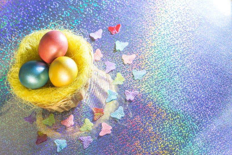 Pasen Multicolored Geschilderde eieren van gele, roze, groene, turkooise parelkleur in een mand op een holografische regenboogach stock foto's