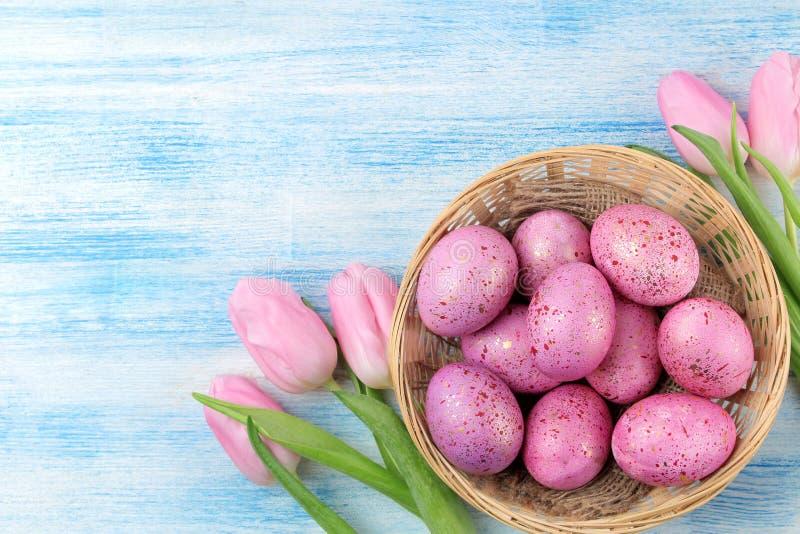 Pasen Roze paaseieren in een mand en bloementulpen op een blauwe houten lijst Gelukkige Pasen vakantie Hoogste mening royalty-vrije stock foto's