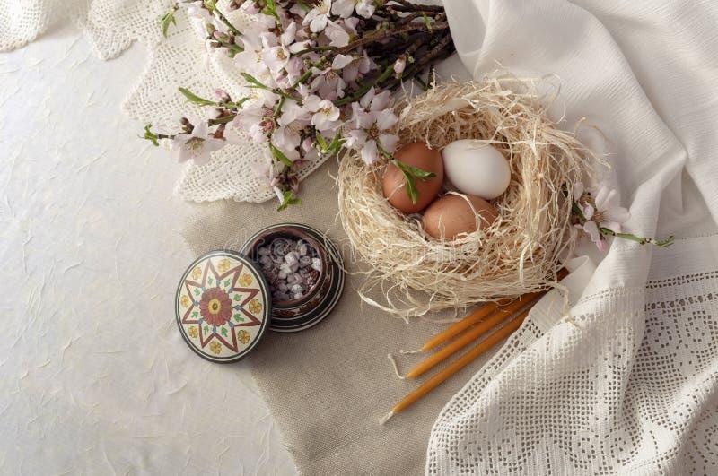 Pasen-samenstelling met eieren in een nest, kerkkaarsen, wierookhars en takken van bloeiende amandelen royalty-vrije stock fotografie