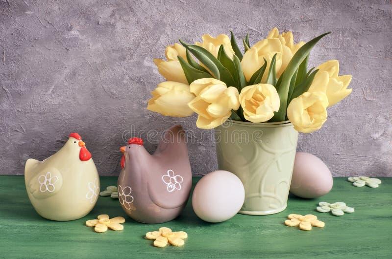 Pasen-samenstelling met gele tulpen, voelde bloemen, ceramische kip royalty-vrije stock afbeelding