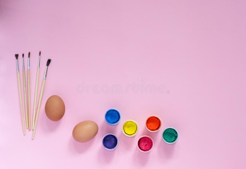 Pasen-samenstelling met schilderijen, borstels en kippeneieren die voor kleuring op roze met copyspace van hoogste mening voorber stock afbeelding