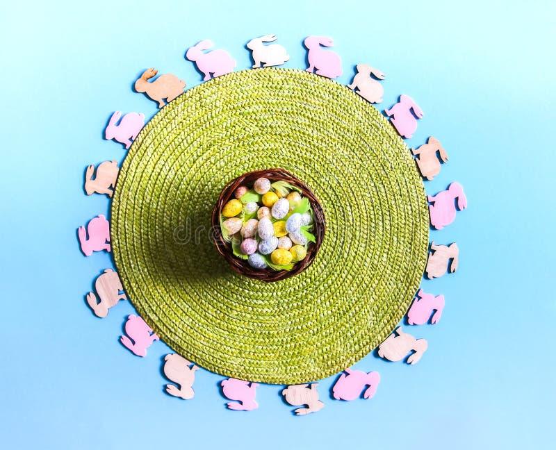 Pasen-samenstelling met traditioneel decor Kleine decoratieve kleurrijke houten konijncijfers en groen rieten onderleggertje royalty-vrije stock fotografie