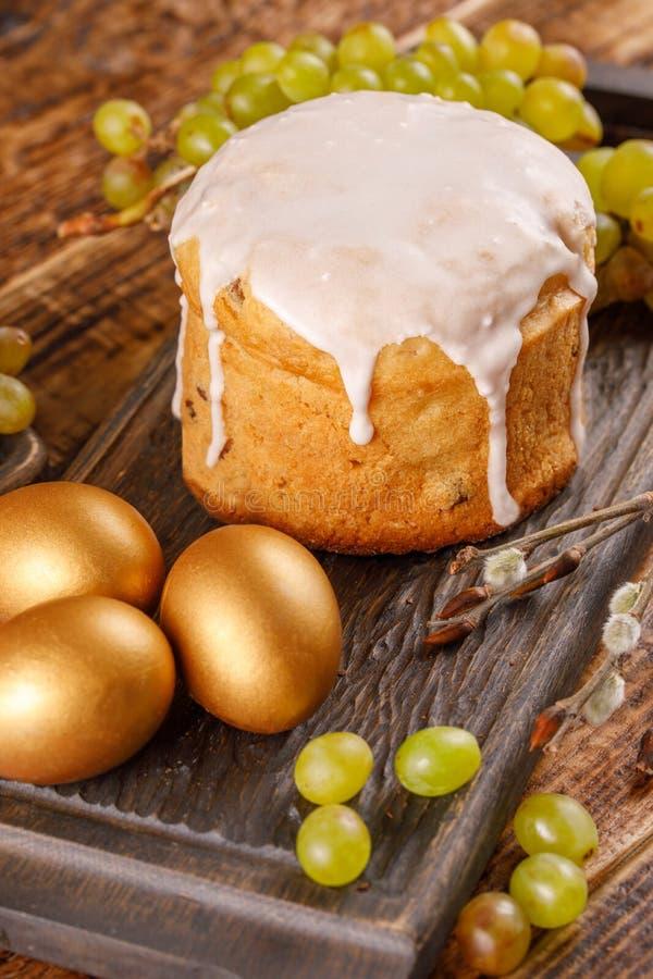 Pasen-samenstelling met traditioneel Russisch Pasen-brood kulich, de gouden eieren van Pasen en druiven op lijst stock afbeelding