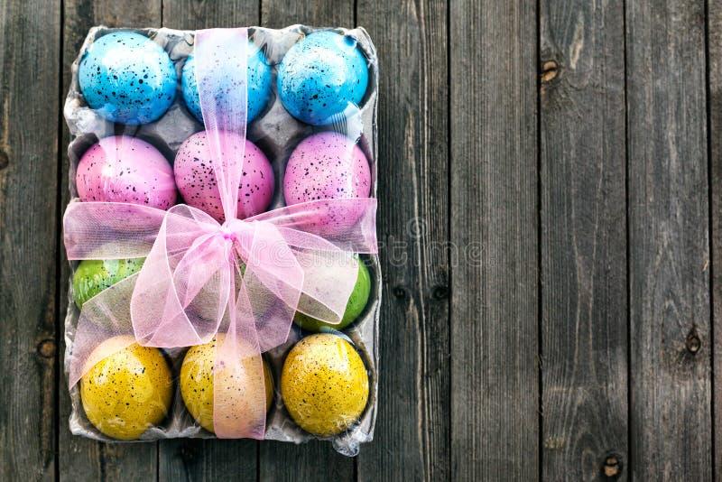 Pasen-stilleven met traditionele decoratieve eieren kleurde in groen, geel, blauw en roze op houten achtergrond stock afbeelding