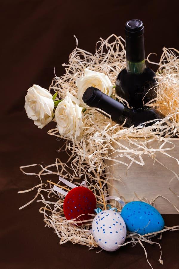 Pasen toe twee nam de de eierendoos van de flessenwijnstok lade de houten blauwe witte rode strosplinters de weinig gele Nederlan stock fotografie