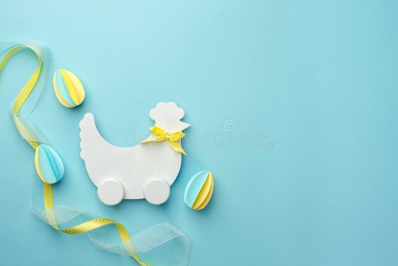 Pasen-vakantie creatieve achtergrond met papercrafteieren, witte houten kip hun op pastelkleur blauwe lijst, in document ambachtv stock fotografie