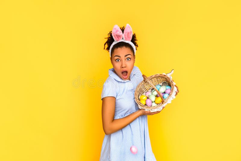 Pasen-vieringsconcept Jonge vrouw in leuke kleding en konijntjesoren status geïsoleerd op geel met mand van eieren royalty-vrije stock foto