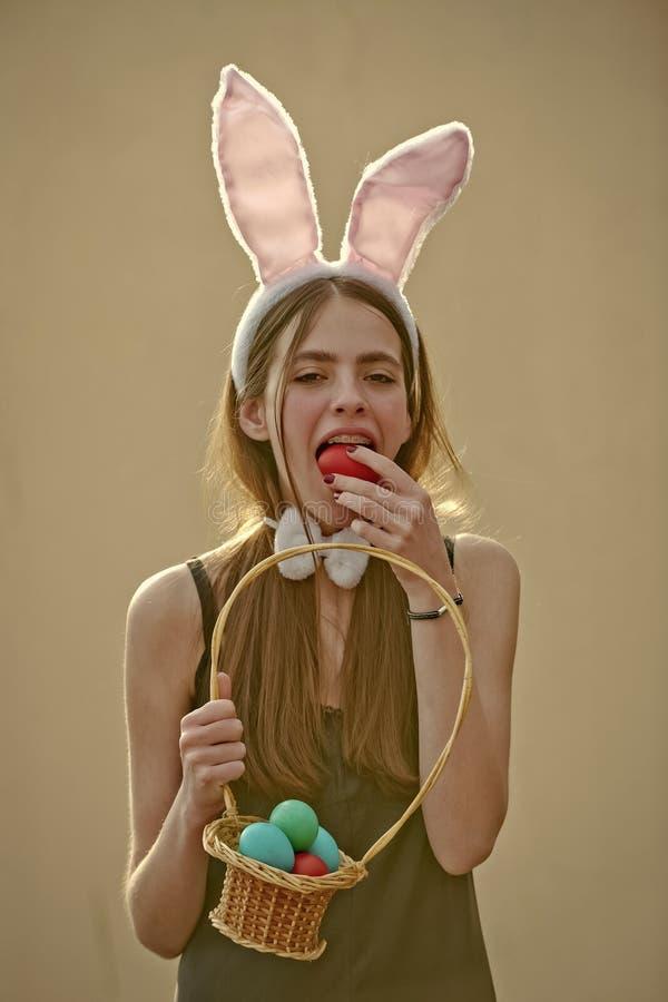 Pasen-vrouw met rieten mand het bijten ei op beige achtergrond royalty-vrije stock fotografie
