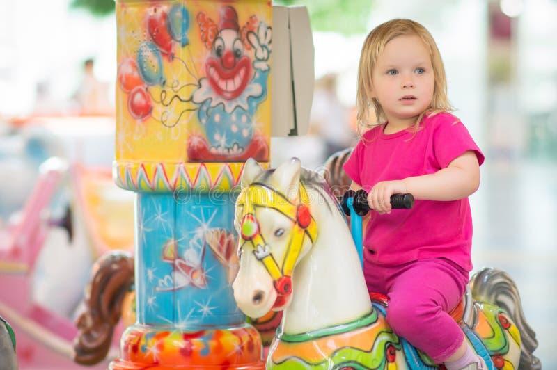 Paseo adorable del bebé en el carrusel en alameda fotografía de archivo