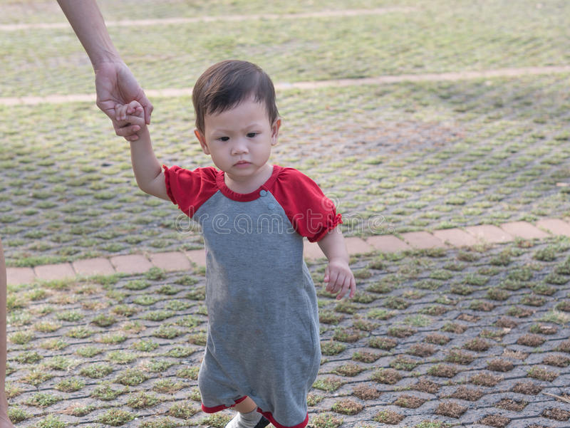 Paseo asiático del niño en verano al aire libre de la mañana del parque imagenes de archivo