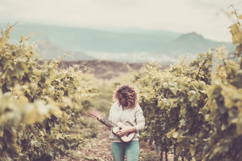 Paseo caucásico hermoso agradable de la mujer solamente en el fondo del verde del viñedo que canta a un ukelele la guitarra acúst fotos de archivo