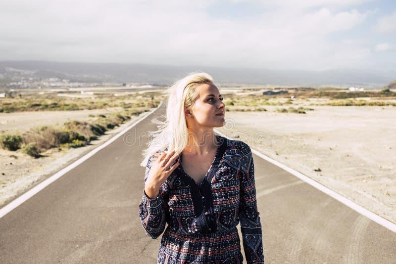 Paseo caucásico rubio solo hermoso de la chica joven en vestido de la moda en un largo camino en el medio del desierto Viaje y foto de archivo