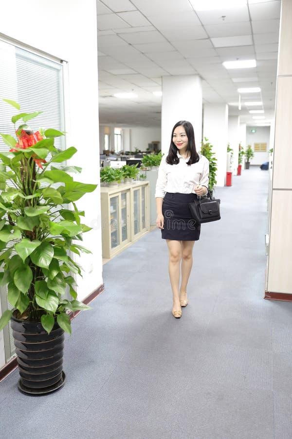 Paseo chino de la muchacha de la mujer de la señora de la oficina de Asia en oficina en el lugar de trabajo del traje del empleo  imagen de archivo