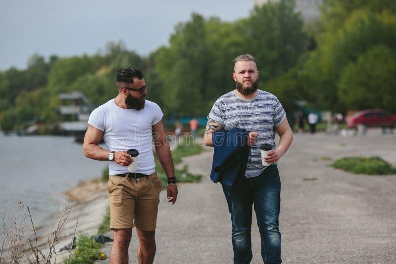 Paseo de dos hombres y café de la bebida foto de archivo