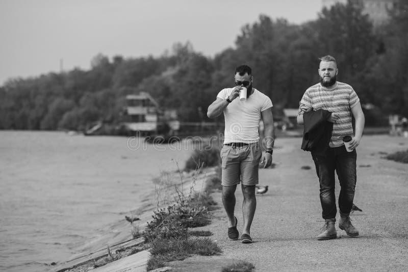 Paseo de dos hombres y café de la bebida imagen de archivo