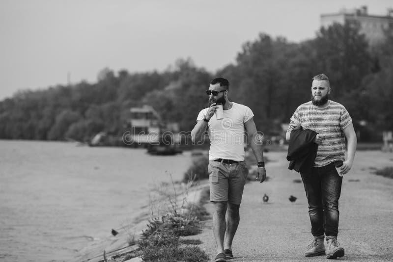 Paseo de dos hombres y café de la bebida fotos de archivo libres de regalías