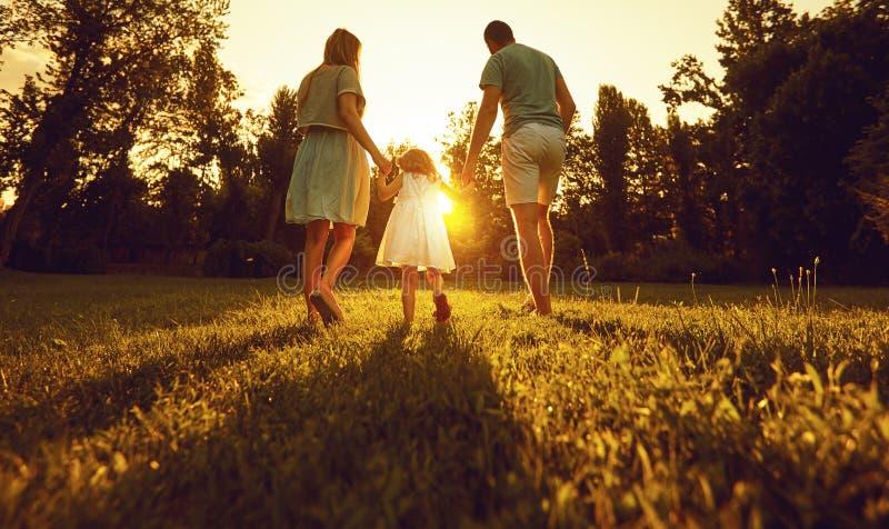 Paseo de la familia con un niño en la puesta del sol en la naturaleza imagen de archivo libre de regalías