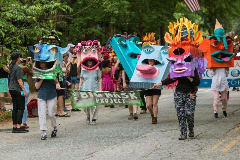 Paseo de la gente en el desfile que lleva máscaras creativas enormes en las cabezas imagen de archivo