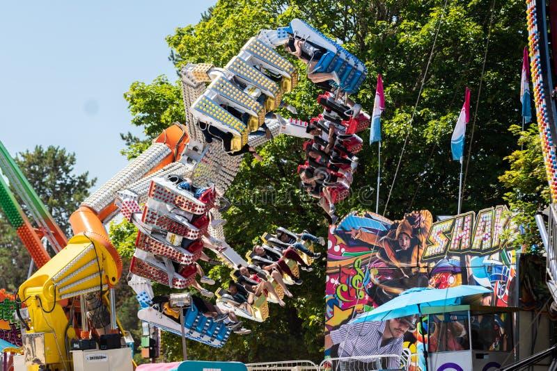 Paseo de la montaña rusa de la garra con la gente de griterío en el parque de atracciones foto de archivo libre de regalías