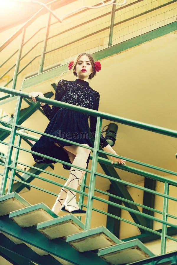 Paseo de la muchacha en las escaleras viejas de la casa en vestido negro foto de archivo libre de regalías
