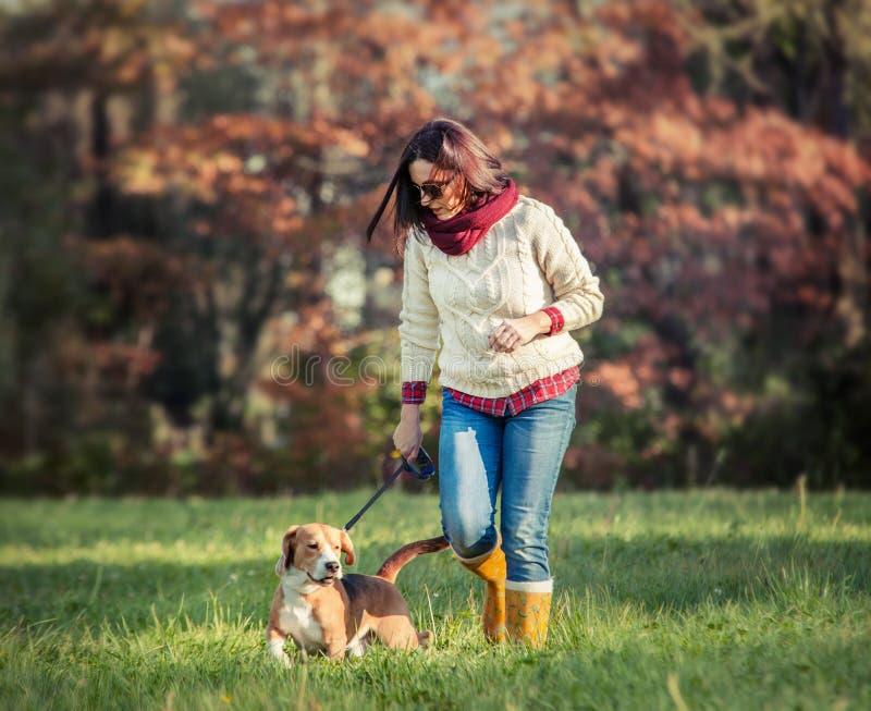 Paseo de la mujer con el perro imágenes de archivo libres de regalías
