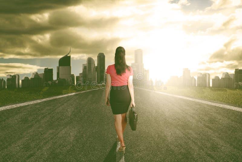 Paseo de la mujer de negocios del éxito hacia el título ligero a la ciudad foto de archivo