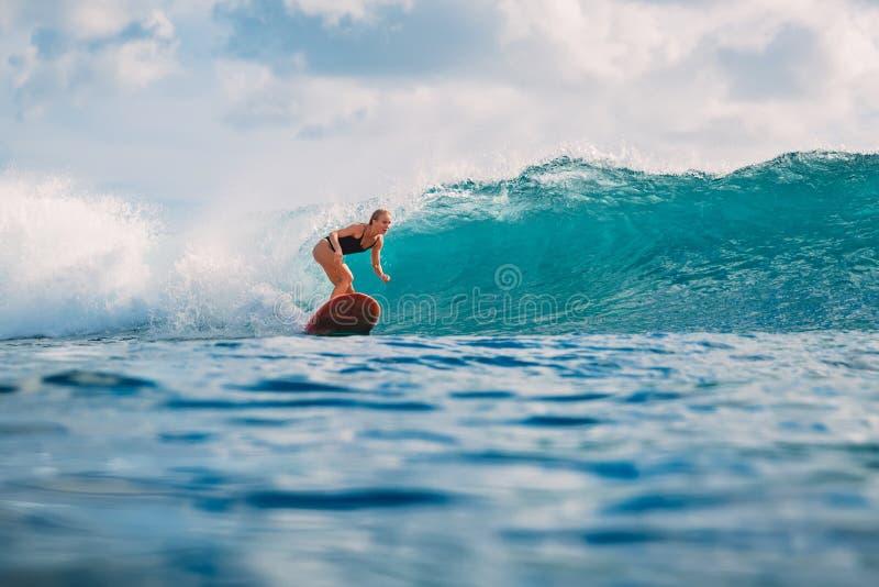 Paseo de la mujer de la resaca en la tabla hawaiana Mujer en el océano durante practicar surf Persona que practica surf y ola oce foto de archivo