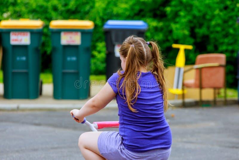 Paseo de la niña una bici rosada de la parte posterior en parque fotografía de archivo