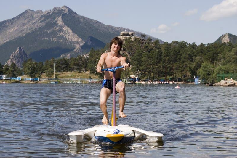 Paseo del adolescente en bicicleta del agua imagen de archivo libre de regalías