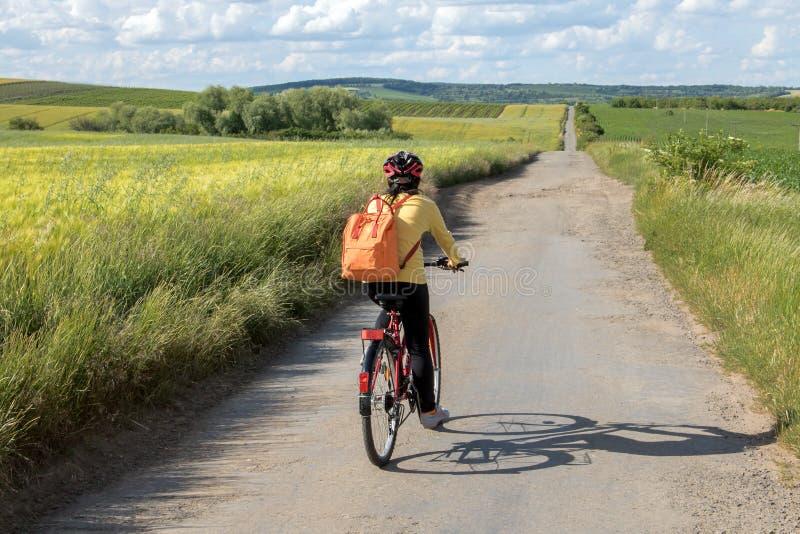 Paseo del ciclista de la mujer de la vista posterior en la bici en el camino de tierra fotos de archivo libres de regalías