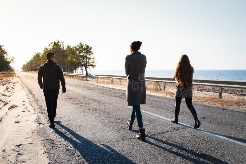Paseo del grupo de personas a lo largo del camino en la playa Tres jóvenes imagen de archivo