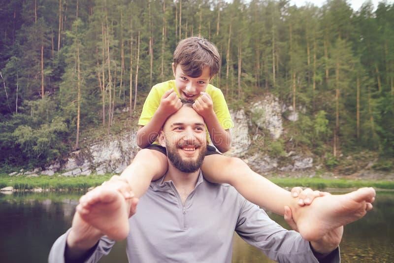 Paseo del padre y del hijo cerca del río imagenes de archivo