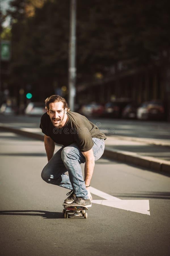Paseo del skater una cuesta del monopatín a través de la calle de la ciudad imágenes de archivo libres de regalías
