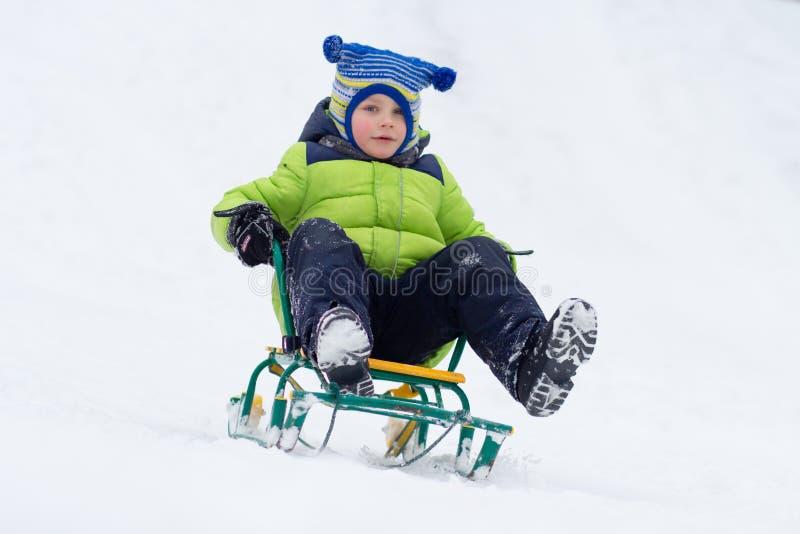 Paseo del trineo del niño pequeño en la montaña de la nieve en invierno imagen de archivo