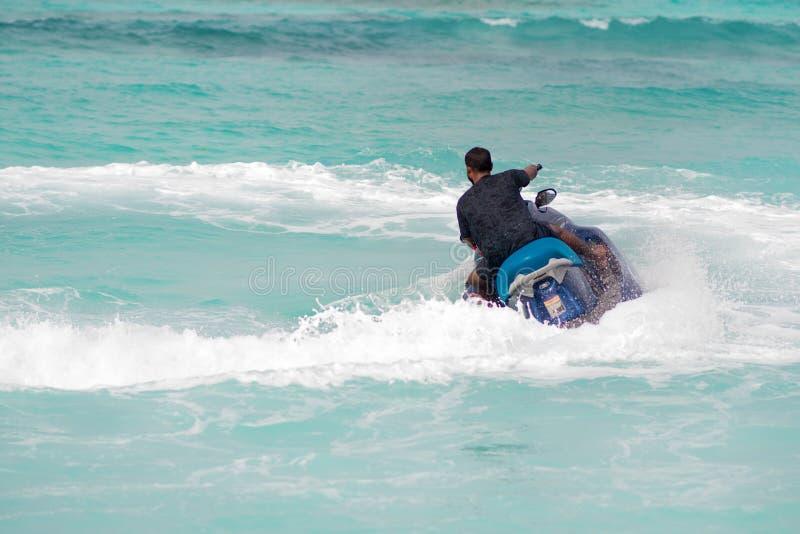 Paseo en un jetski el hombre en una vespa del agua hace una vuelta foto de archivo