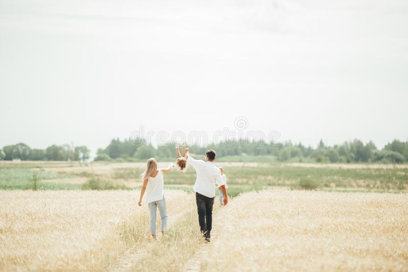 Paseo feliz de la familia en campo de trigo el día soleado imagenes de archivo