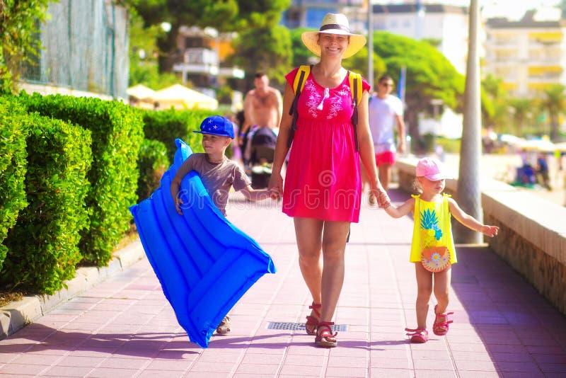 Paseo feliz de la familia a la playa del mar fotografía de archivo