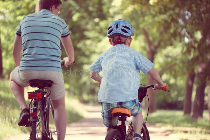 Paseo feliz del padre y del hijo en las bicis fotos de archivo libres de regalías