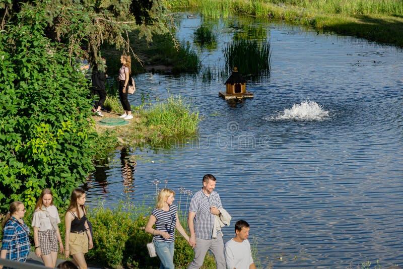 Paseo feliz joven de la gente cerca de la charca hermosa en el parque de Zaryadye imagen de archivo